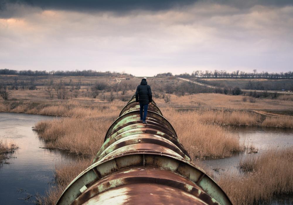 Man walking on a pipeline